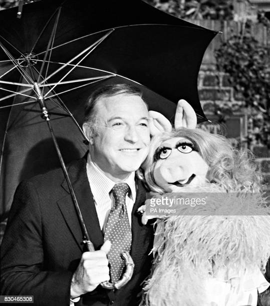 Hollywood song and dance star actor Gene Kelly sharing his umbrella with new dancing partner Miss Piggy of The Muppet Show at ATV Studios in Boreham...
