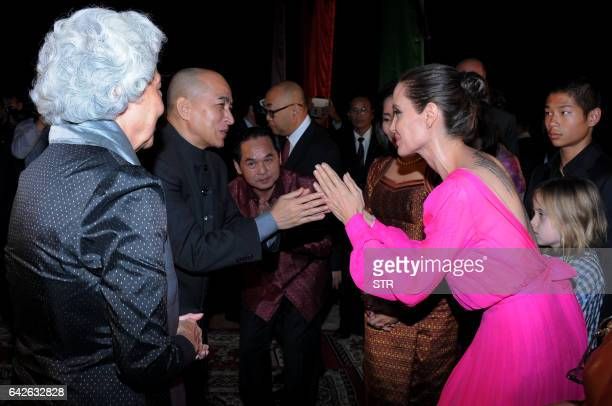 Hollywood star Angelina Jolie pays respect to Cambodian King Norodom Sihamoni as former queen Monique looks on during the premiere of Jolie's new...