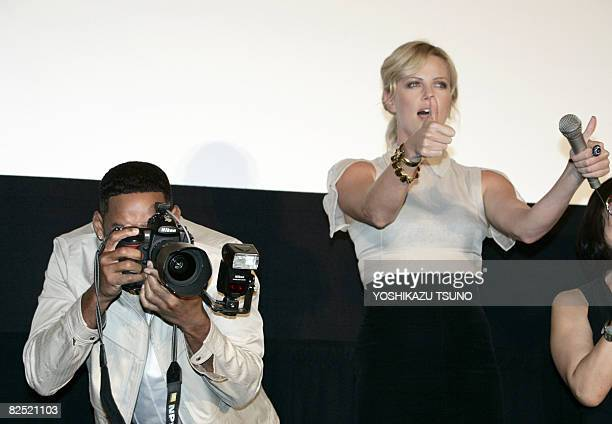 Hollywood star Will Smith uses the camera of a press photographer for a joke during the premier of his latest movie 'Hancock' at a Tokyo theater on...