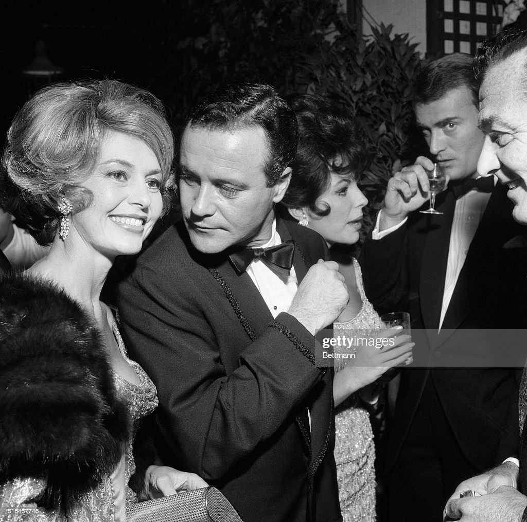 Hollywood stars Cyd Charisse (left), Jack Lemmon and Joan Collins (right) enjoy themselves during a party at the Grand Hotel in Rome, October 14th. The huge party, which was attended by a large number of international; stars, was given by actress Elizabeth Taylor for actor Kirk Douglas. The party celebrated the first anniversary of Douglas' film, Spartacus.