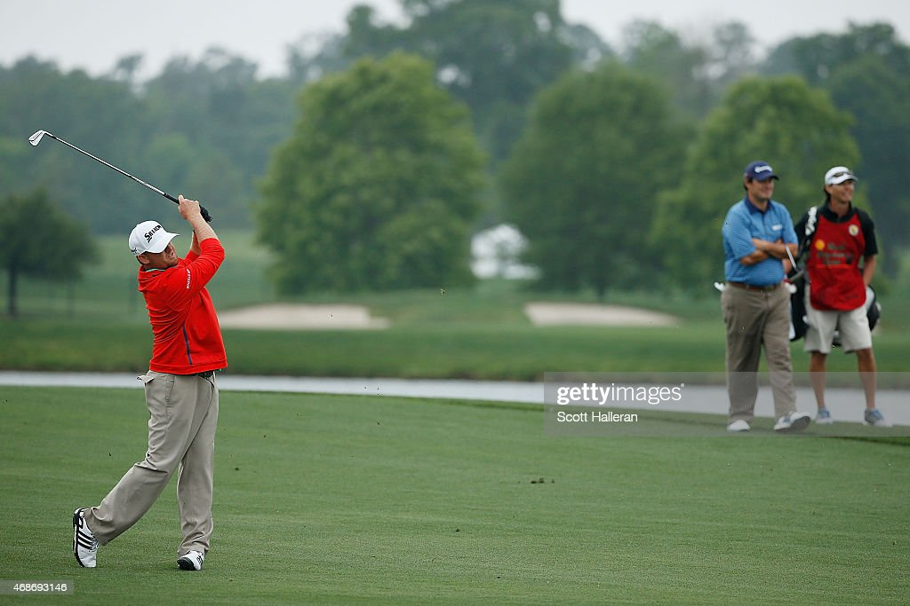 B Holmes hits his second shot of the second playoff hole as Johnson Wagner and his caddie look on at the Shell Houston Open at the Golf Club of...