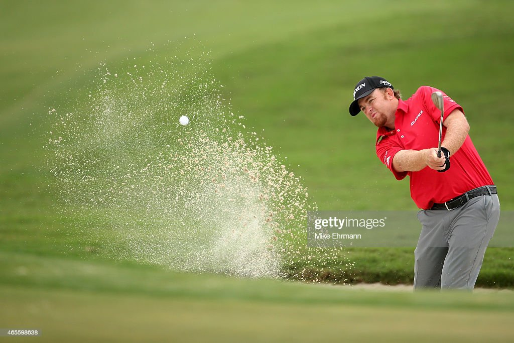 J B Holmes of the United States plays his shot out of the bunker on the sixth hole during the final round of the World Golf ChampionshipsCadillac...