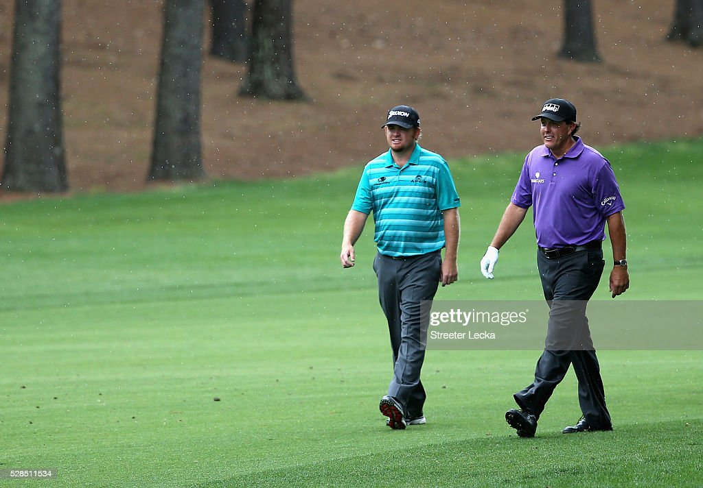 J.B. Holmes walks with Phil Mickelson up the third fairway during the first round of the 2016 Wells Fargo Championship at Quail Hollow Club on May 5, 2016 in Charlotte, North Carolina.