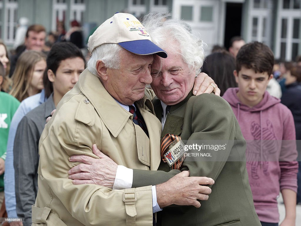 Holocaust survivors US Andrew Sternberg (L) and Russian Vassily Kononenko embrace each other during a commemoration of the liberation of the Nazi concentration camp Mauthausen on May 12, 2013, 160 kilometers near Vienna. AFP PHOTO / DIETER NAGL