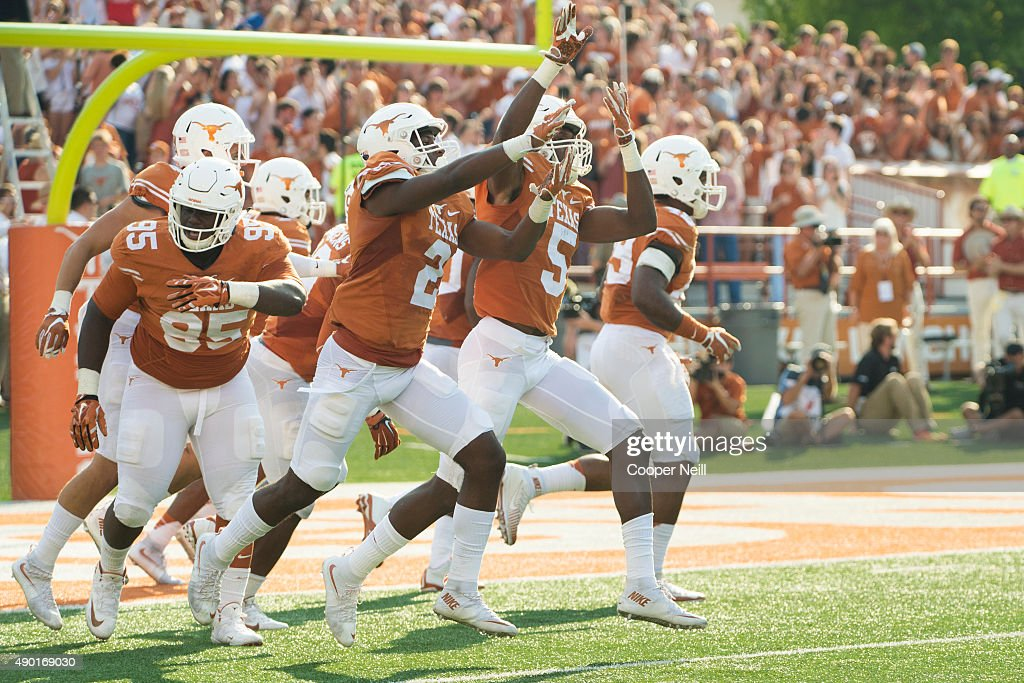 Holton Hill of the Texas Longhorns celebrates with teammates after intercepting the ball and returning it 41 yards for a touchdown against the...