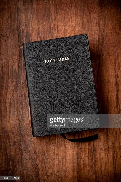 Holy Bible in Black Leather on Wood Background