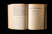 An overhead view of an old bible opened to The New Testament.