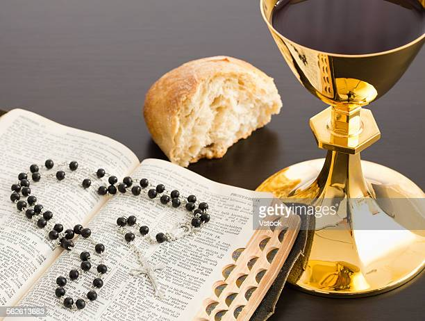 Holy Bible with black rosary beads, bread and gold chalice with wine