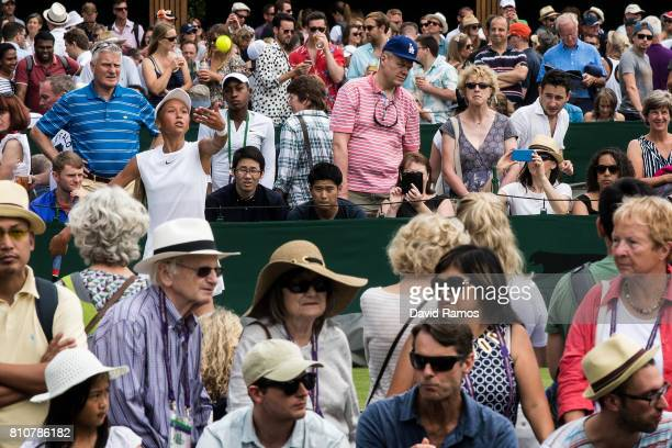 Holy Fisher of Great Britain serves against Mai Hontama of Japan as spectators follow the action around the oudide courts on day six of the Wimbledon...