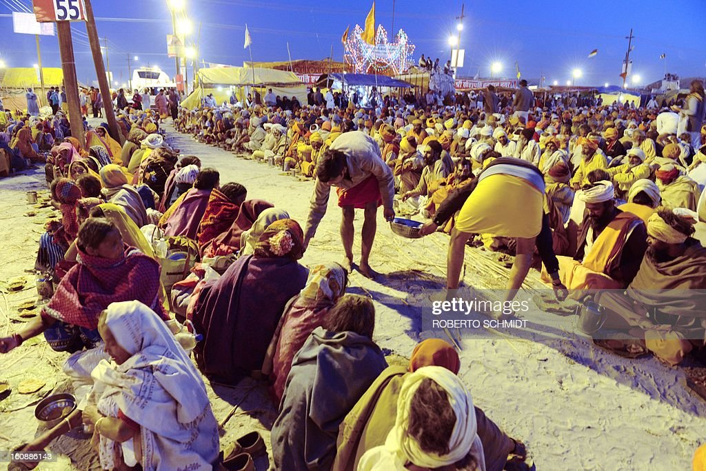 Holy men called Sadhus and Hindu devotees are served a meal as they sit near the shore of the confluence of the Yomuna and the Ganges river at the Sangam in the early evening as they wait to be served a free meal organized by an ashram during the Maha Kumbh festival in Allahabad on February 7, 2013. The Kumbh Mela in the town of Allahabad will see up to 100 million worshippers gather over 55 days to take a ritual bath in the holy waters, believed to cleanse sins and bestow blessings.