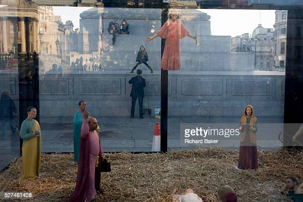 A holy nativity scene titled Christmas Crib by the artist Tomoaki Suzuki with background tourists in London's Trafalgar Square Juxtaposed under the...