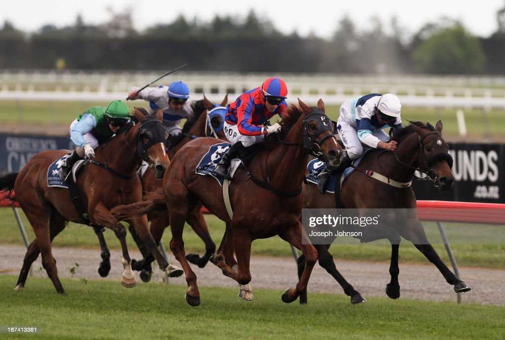 Holy Smoke, with jockey Mark Du Plessis, wins the The Paintlab Hornby Premier race with Black Stockings with jockey Chris Johnson running second on the inside during New Zealand 2000 Guineas Day on November 9, 2013 in Christchurch, New Zealand.