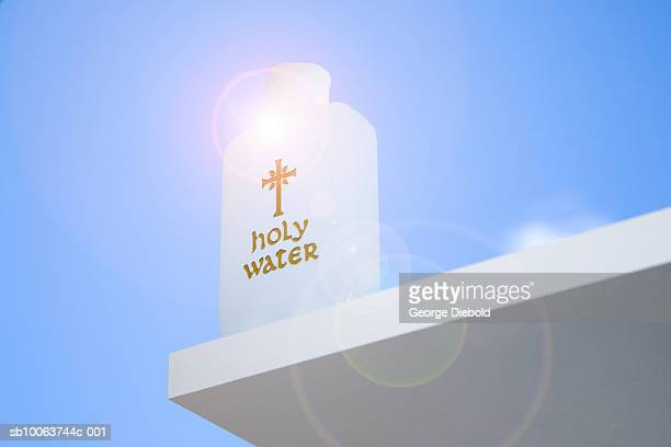 Holy water on table with sun behind, low angle view (lens flare)