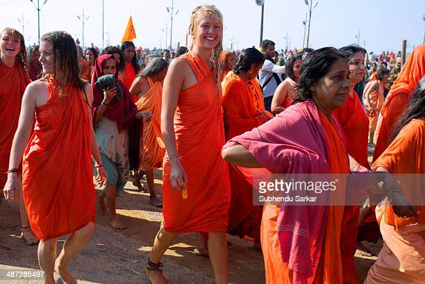 Holy women of European origin move in procession after taking holy dip at the confluence of the rivers Ganges and Yamuna Kumbh Mela is a site of mass...
