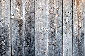 Braun graue Holzbretter von einer alten Scheune die oben und unten mit Nägel befestigt wurden.