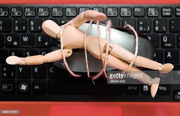 Holzpuppe auf Computermouse gefesselt und Computer Symbolfoto kinderpornografische Fotos im Internet