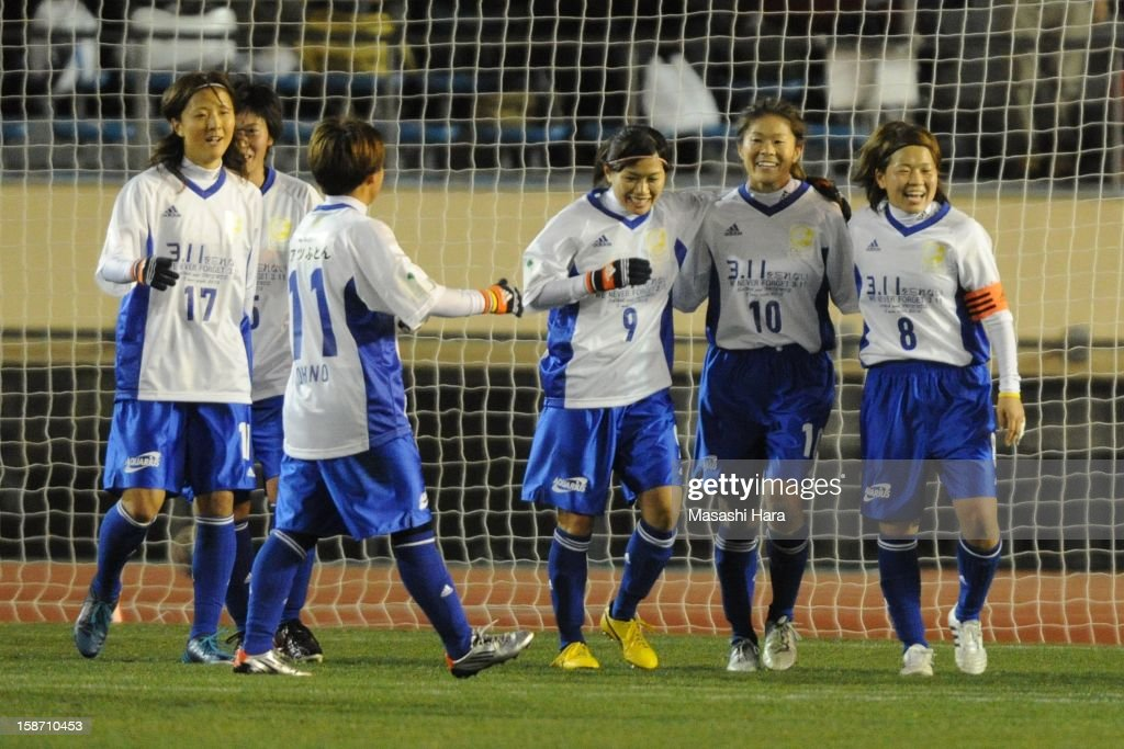 Homare Sawa (2 R) celebrates her goal with team-mates during the Great East Japan Earthquake charity match 'SAWA and Friends, X'mas Night 2012' at the National Stadium on December 25, 2012 in Tokyo, Japan.