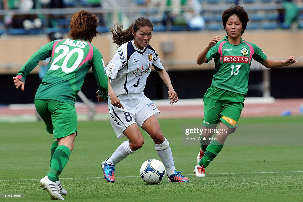 Homare Sawa of INAC Kobe Leonessa competes for the ball with Mizuho Sakaguchi (L) and Mana Iwabuchi (R) of NTV Beleza during the Nadeshiko League match between NTV Beleza and INAC Kobe Leonessa at the National Stadium on June 10, 2012 in Tokyo, Japan.