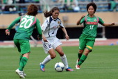 Homare Sawa of INAC Kobe Leonessa competes for the ball with Mizuho Sakaguchi and Mana Iwabuchi of NTV Beleza during the Nadeshiko League match...