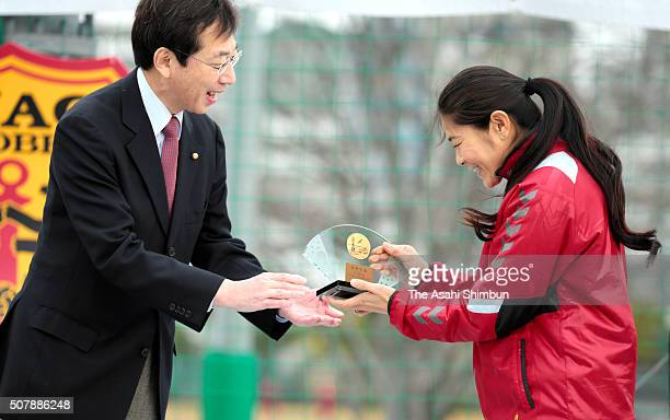 Homare Sawa receives the trophy from Kobe City Mayor Kizo Hisamoto as she is awarded the Kobe City Sports Special Contribution Prize during the INAC...