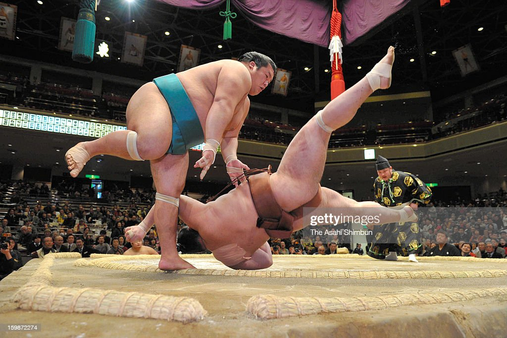 Homarefuji (L) throws Jokoryu to win during day ten of the Grand Sumo New Year Tournament at Ryogoku Kokugikan on January 22, 2013 in Tokyo, Japan.