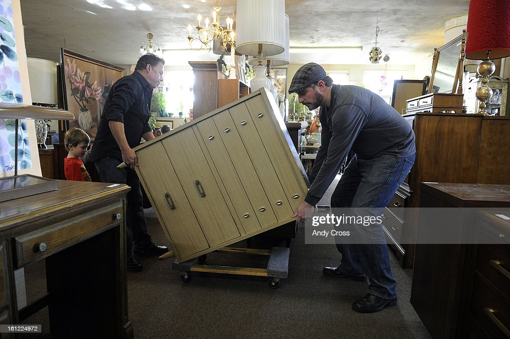 Home   Again furniture store owner  Thom Persson  right  helps customer   Scott Stone and Scott s son  Matthew  3  to move a dresser in his store at  1959 S. Home   Again furniture store owner  Thom Persson  right  helps