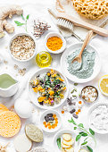 Home beauty products - clay, oatmeal, coconut oil, turmeric, lemon, scrub, dry flowers and herbs, sponges, soap, facial brush on light background, top view. Skin youthfulness, beauty concept. Flat lay