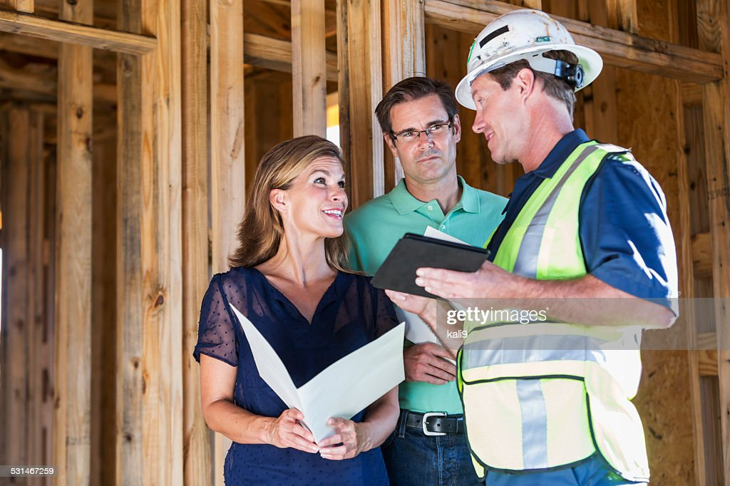 Home builder talking with couple at construction site : Stock Photo