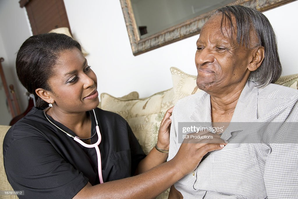 Home Caregiver Checking Heart Rate of Patient : Stock Photo