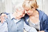 home caregiver consoling sad senior woman