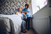 Home Caregiver helping a senior woman get dressed in her bedroom.