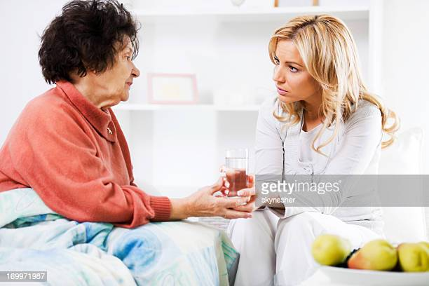 Home caregiver giving a senior woman glass of water