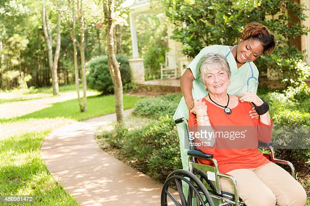 Home caregiver, nurse with senior adult patient outdoors. Nursing home.