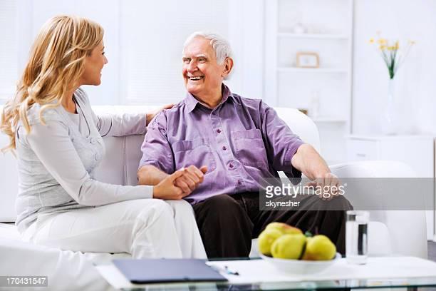 Assistente domiciliare seduta n sul divano con un uomo anziano