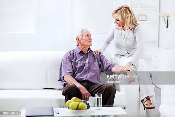 Assistente domiciliare seduto sul divano con un uomo anziano