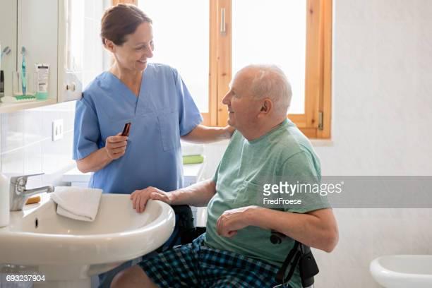 Aide familiale avec homme senior dans salle de bain