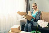 home delivery - smiling young woman opening cardboard box