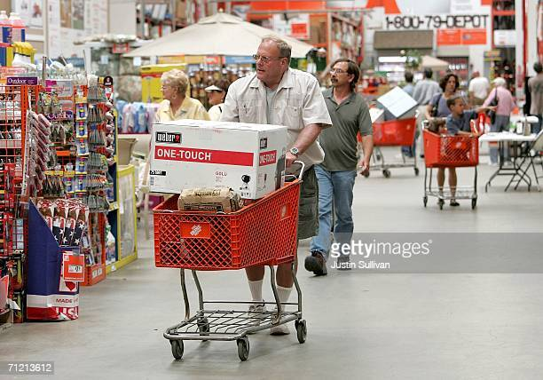 Home Depot customer pushes a shopping cart with a Weber barbecue grill at a Home Depot store on June 15 2006 in San Rafael California Retail outlets...
