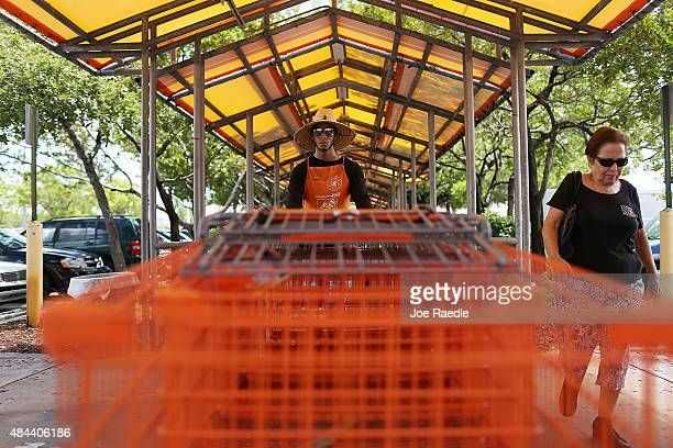Home Depot employee Alex Garcia pushes a row of carts at the store on August 18 2015 in Miami Florida Today Home Depot shares rose as the company...