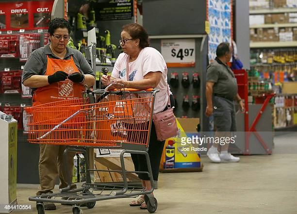 Home Depot employee Flor Raudales helps Margarita Rodriguez as she shops at the store on August 18 2015 in Miami Florida Today Home Depot shares rose...