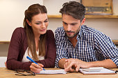 Happy young couple reading and analyzing bills sitting at table. Young couple in casual discussing home economics. Young couple calculating their expenses and incomes.