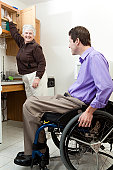 Home health aid getting a glass for a man in wheelchair with spinal cord injury