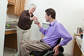 Home health aid offering a glass of water to a man in wheelchair with spinal cord injury