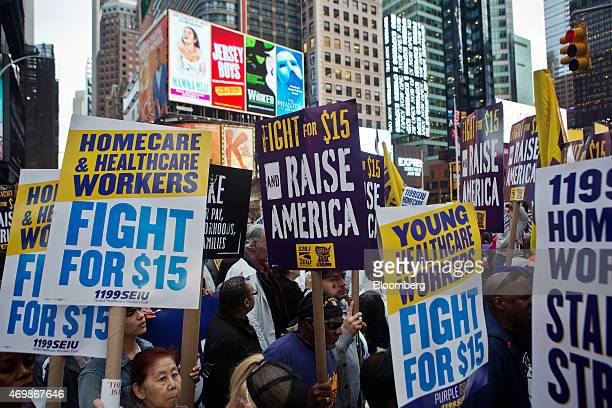 Home health care workers and other protesters hold signs at a rally in support of minimum wage increase in New York US on Wednesday April 15 2015...