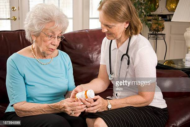 Home healthcare medical professional helps senior woman with pills