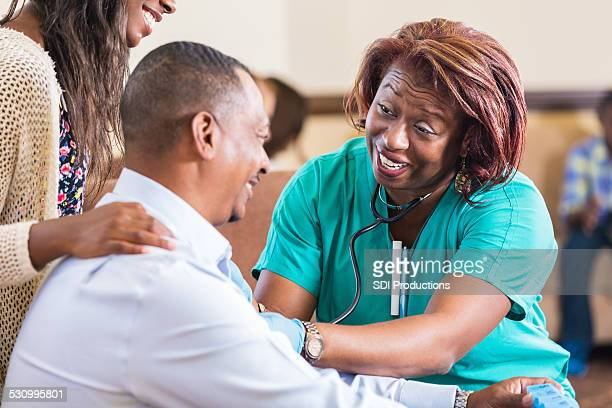 Home healthcare nurse checking blood pressure of mature man