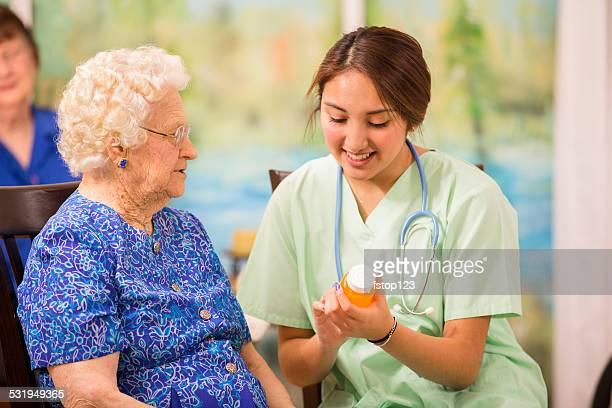 Home healthcare nurse explains prescription medicine to elderly woman.
