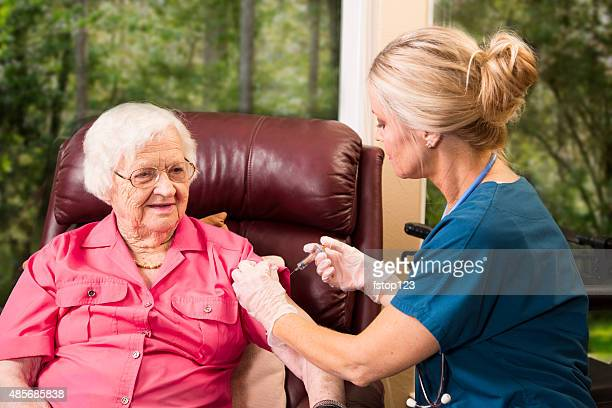 Home healthcare nurse giving injection to elderly woman.