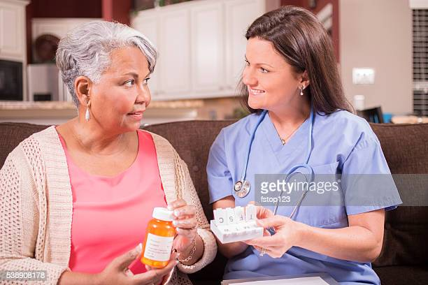 Home healthcare nurse giving medications to senior adult woman.