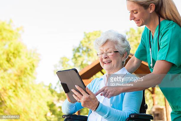 Home healthcare nurse helps patient with digital tablet